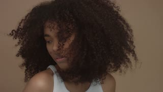 black model with huge curly hair moving shaking hair in slow motion from 60 fps studio shoot