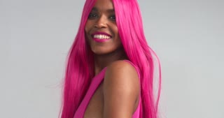 Black women dancing in pink wig