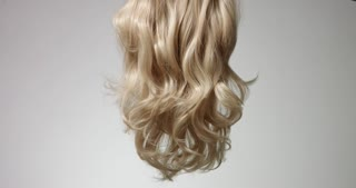 Brushing long wavy woman's blond hair with a hairbrush isolated on white