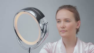 caucasian woman with mirror with ring light with no makeup look examine her skin and makes facial treatment and touching her neck