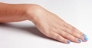 Clean well manicured hands of a young woman, applying hand cream, skin care on white background close up