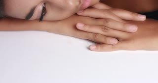 Close up shot of a pretty young wooman with smooth glowing skin relaxing on a white massage table. tilt movement