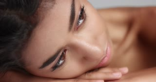 Close up shot of a pretty young wooman with smooth glowing skin relaxing on a white massage table