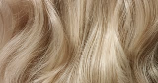 Close up shot of brushing long wavy woman's blond hair with a hairbrush