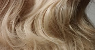 Close up video of shaking long blond wavy woman's hair