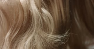 Close up video of woman's long wavy blond hair