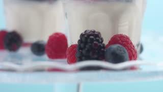 c,loseup of berries and glasses with greek yogurt on blue background. Minimalism food video