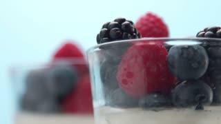 closeup of berries decoration of dessert in transparent glass full of panna cotta or greek yogurt
