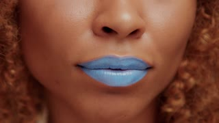 closeup of black womans mouth with bright blue lipstick smiling