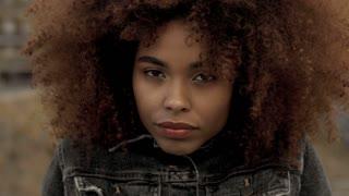 closeup of mixed race black woman wears black denim jacket and feeling freeze lift up jacket collar