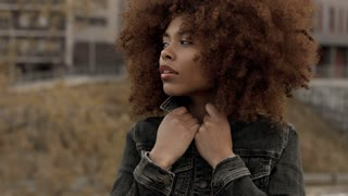 closeup of mixed race black woman wears black denim jacket and feeling freeze lift up jacket collar
