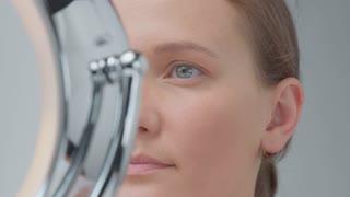 closeup of woman's eye. woman put under eye cream and massage skin
