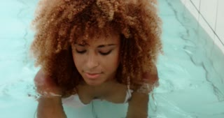 closeup portrait of black woman with big afro hair in swimming pool