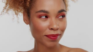 closeup womans face with red makeup posing to the camera