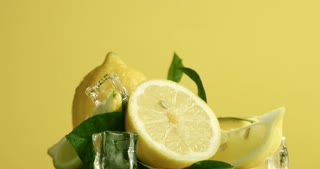 composition of lemons, leaves and ice cubes. Covered by water drops. Fresh summer fruit composition