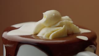 cup of hot chocolate with a cream and liquid white chocolate pouring on it. CLoseup of turning cup