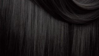 Hair texture background, no person. Black shiny hair curl falling down