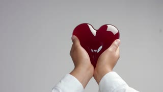 jelly-like red heart in man's hand holding it gently