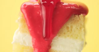 lemon cake slice on a fork with a cream and fruit topping pouring on