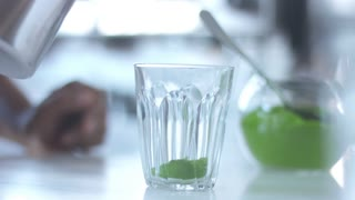 matcha tea preparation in glass with electric blender mixer