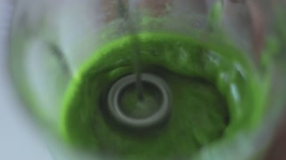 matcha tee closeup mixing in transparent glass with electric mixer