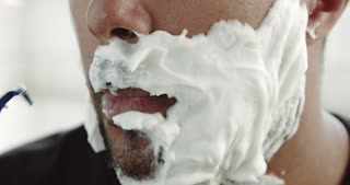 mixed race black man shaving with foam