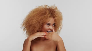 mixed race woman with big curly afro blonde hair hide her mouth behind her hands and then show it up