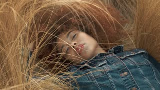 mixed race woman with huge curly hair lying down on lawn with high dry grass