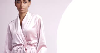 Pan video of a pretty young girl with black hair in a pink silk dressing gown in a cosmetology clinic