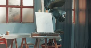 Pan video of an artist's studio with brushes, pencils, markers and other tools and a blank canvas on an easel
