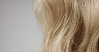 Pan video of woman's long wavy blond hair on white background