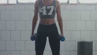 perfect fit black woman makes a squats witha weight workout showing perfect body in sunny loft
