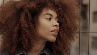 portrait of mixed race black woman in total denim look in industrial zone