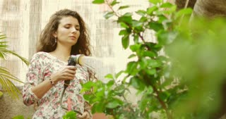 Pretty long-haired girl in cute floral dress watering plants in her patio garden