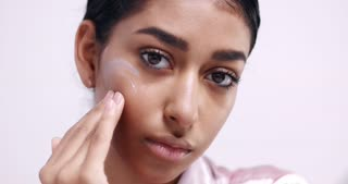 Pretty young Moroccan woman putting face cream on her cheeks and massages it into the skin isolated on white