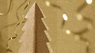 Seamless golden sparkling background. Shiny glitter 3 dimensional carton Christmas tree is turning around with glossy bright curly ribbons around. Still horizontal shot high quality 4k video.