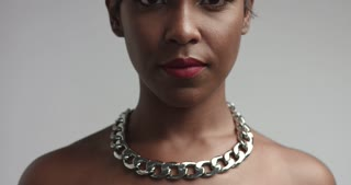 Sexy confident African American model wearing a trendy black leather dress, large chain necklace and heavy bracelet on white background