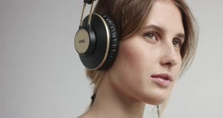 Smiling attractive girl listening to music in headphones on white background