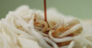soy sauce pouring on rice noodles