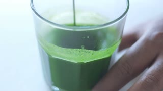 strong green matcha tee in transparent glass preparation process