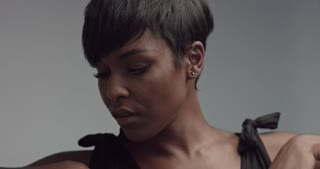 Strong powerful dance of a cute feminine black girl with pixie cut shot in slow motion isolated on gray