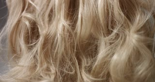 Styling long wavy blond hair with hairspray, close up shot