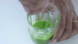 top view of glass with matcha tee preparing using electric mixer