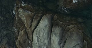 Top view showing plane rocks and a transparent clean sea water with a water-plants in it moving
