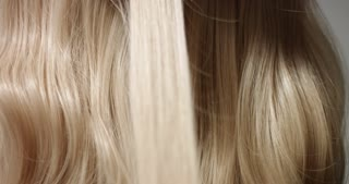 Using a black hair straightener to style long blond wavy woman's hair, close up video