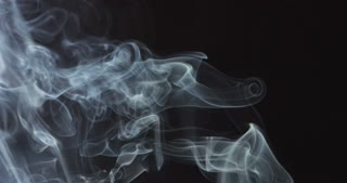 Wisps of white smoke swirling in the air on white background