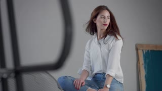 woman in industrial studio wears jeans and white shirt blowing long hair rose bright lips. Classick jeans outfit