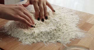 woman makes a dough on a wooden tablet. closeup