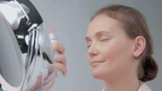 woman using a facial mist spray sitting behind the mirror