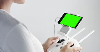woman with a white remote controller of drone with smartphone with a green screen